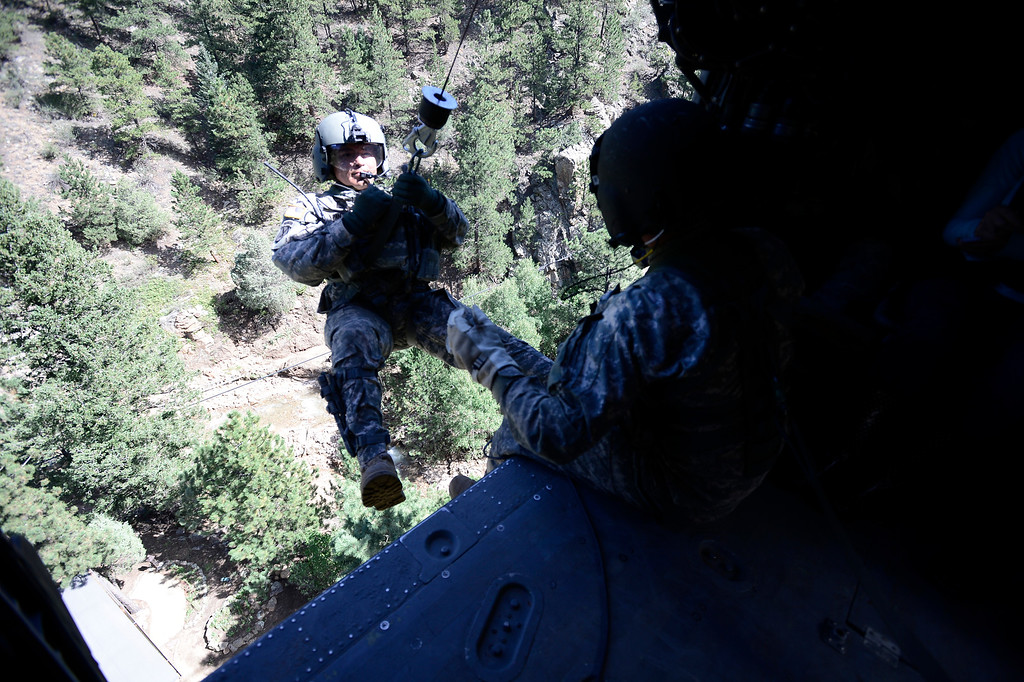 . Staff Sgt. Jose Pantoja goes out the helicopter door on a rescue mission outside Jamestown Colorado which was hard hit by flood waters. The helicopter was flown by members of 2-4 GSAB 4th Infantry Division based in Ft. Carson, Colorado Tuesday September 17, 2013. BOULDER DAILY CAMERA/ Mark Leffingwell
