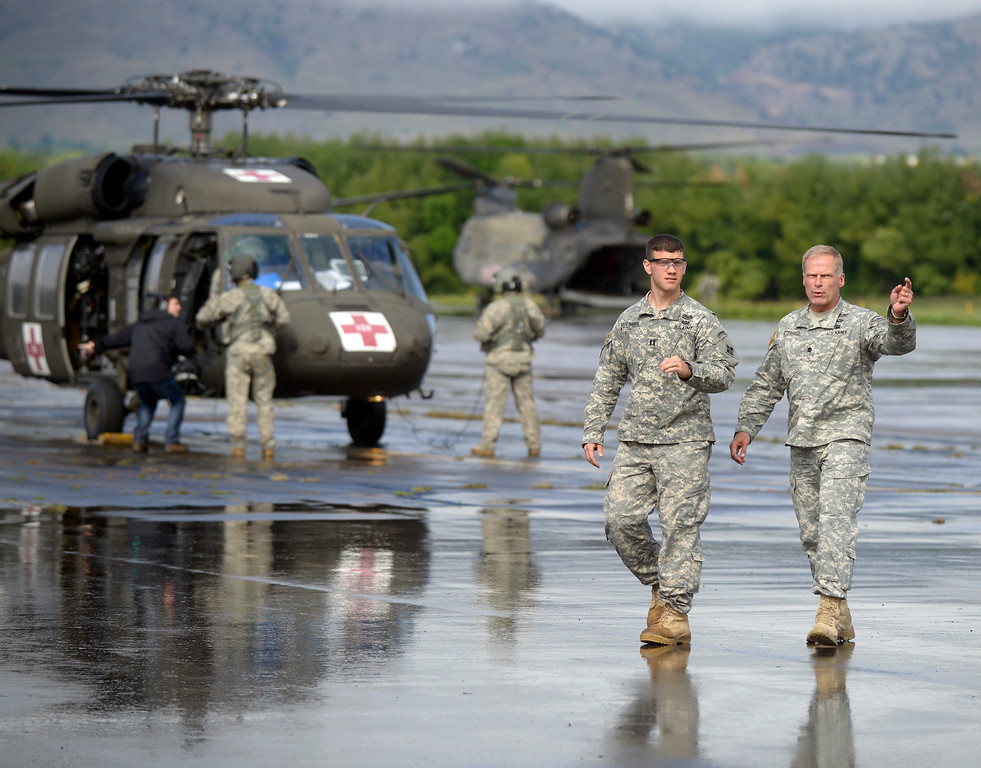 . U.S. Army Lt. Colonel Mitch Utterback, at right, talks with another officer, not identified, as the first military helicopters of the day head out on rescue missions on Monday, Sept. 16, at the Boulder Municipal Airport in Boulder. For more photos and video of the flood rescue go to www.dailycamera.com Jeremy Papasso/ Camera