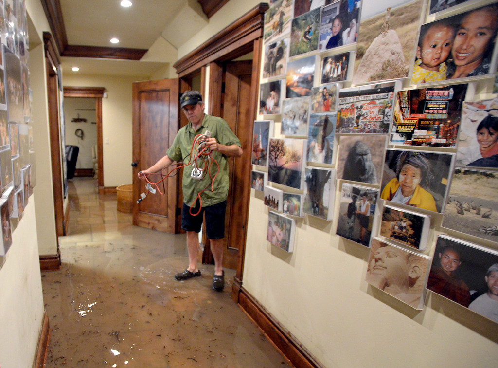 . Chris Drummond, of Boulder, walks through his flooded basement during the heavy flooding on Thursday in Boulder. For a video of the flooding go to www.dailycamera.com  Jeremy Papasso/ Camera