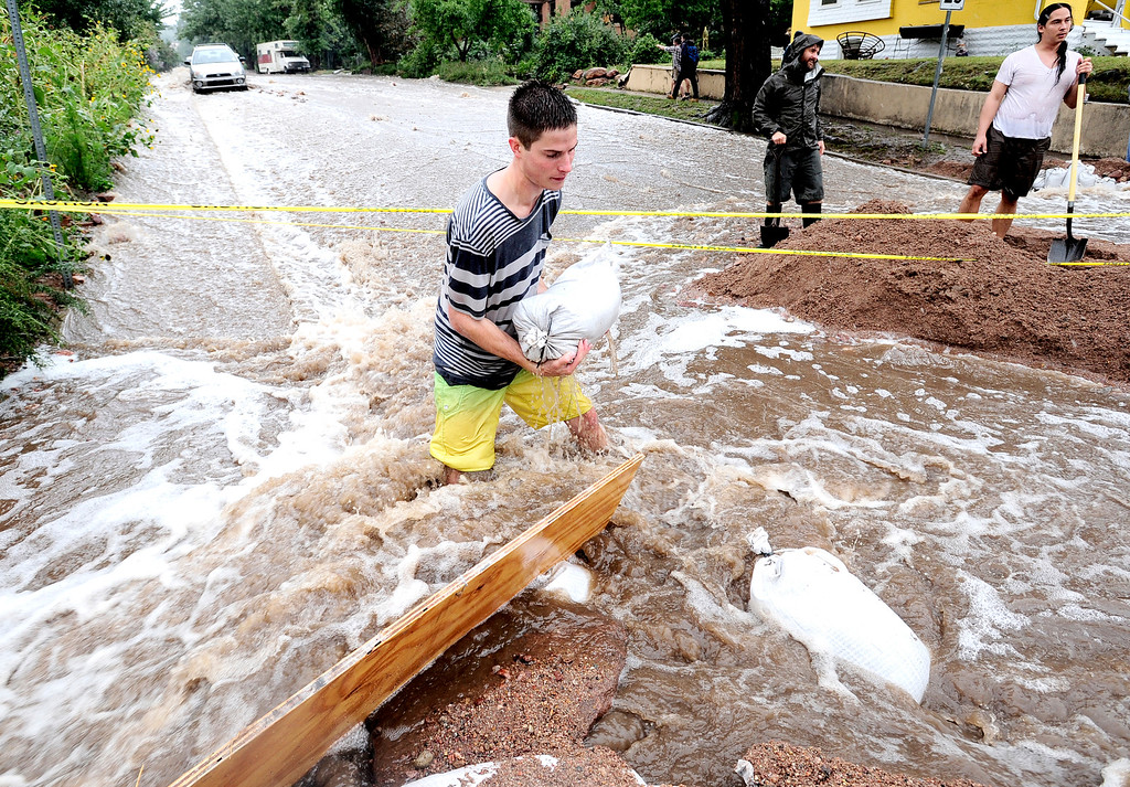 . Jake Bennett moves a sand bag to help funnel water down 7th Street at University as heavy rains cause severe flooding in Boulder, Colorado September 12, 2013. BOULDER DAILY CAMERA/ Mark Leffingwell