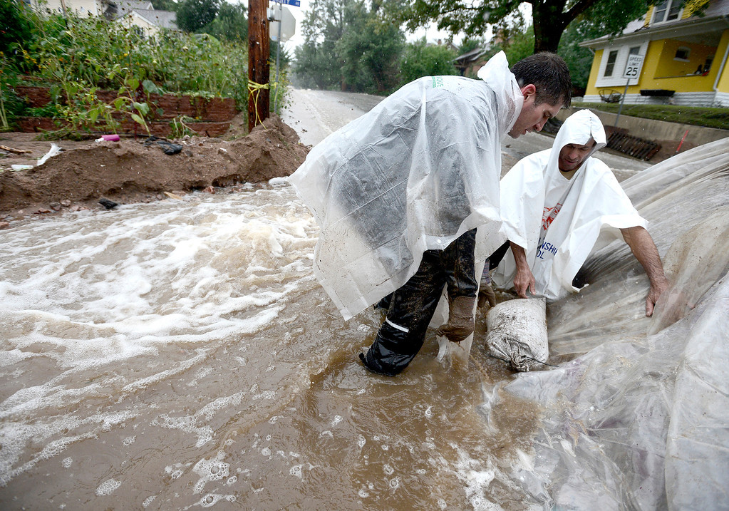 . Ed von Bleishert (L) and Scott Hoffenberg (R) use sand bags and plastic sheeting to prevent a berm from washing out as water rise in heavy rains  in Boulder, Colorado September 15, 2013. BOULDER DAILY CAMERA/ Mark Leffingwell