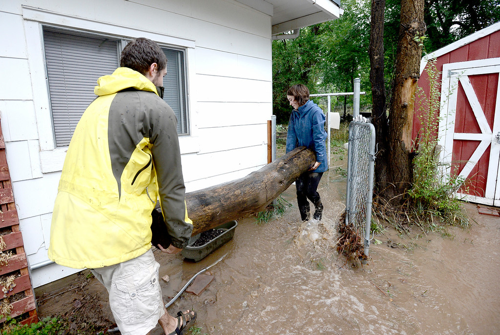 . Levin Sliker (left) and Elizabeth Aisenbrey (right) move logs to try and divert water from running into their home after heavy rains caused floodingin Boulder, Colorado September 13, 2013. BOULDER DAILY CAMERA/ Mark Leffingwell