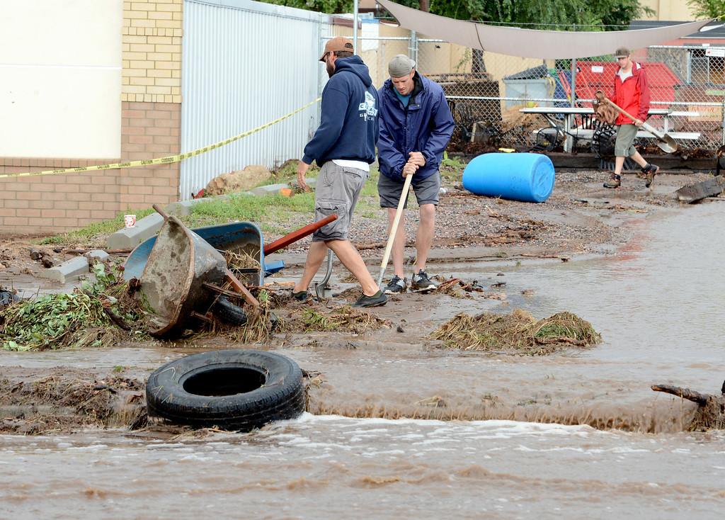 . Brian Frenz, left, and Josh Ford, both of Namaste Solar on North Broadway, move debris off their site. For more flooding videos and photos, www.dailycamera.com. Cliff Grassmick  / September 13, 2013