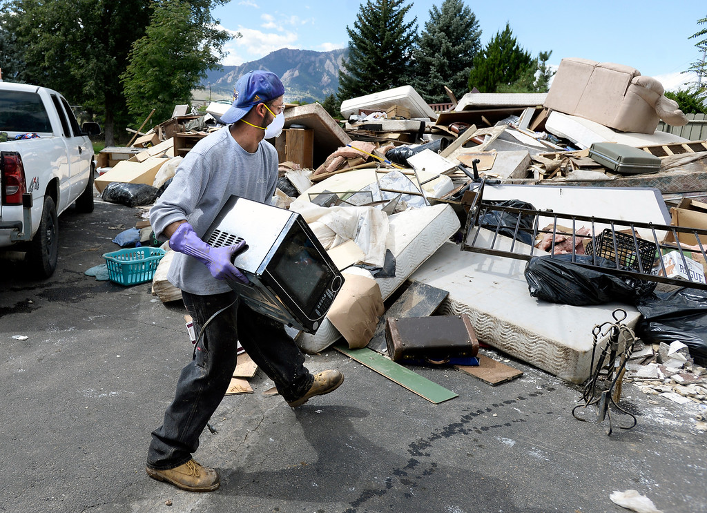 . Adan Zepeda, of Overtime Landscaping, works to clean out damaged belongings in an apartment in the Manhattan West Apartments on Wednesday, Sept. 18, in Boulder. For more photos and video of the flood go to www.dailycamera.com Jeremy Papasso/ Camera