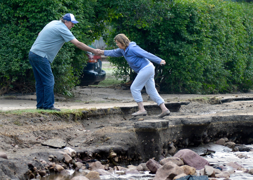 . Steve Wigotow helps his wife Karen jump across a section of broken road on Topaz Drive on Saturday, Sept. 14, in Boulder. For more photos and video of the flood rescue go to www.dailycamera.com Jeremy Papasso/ Camera