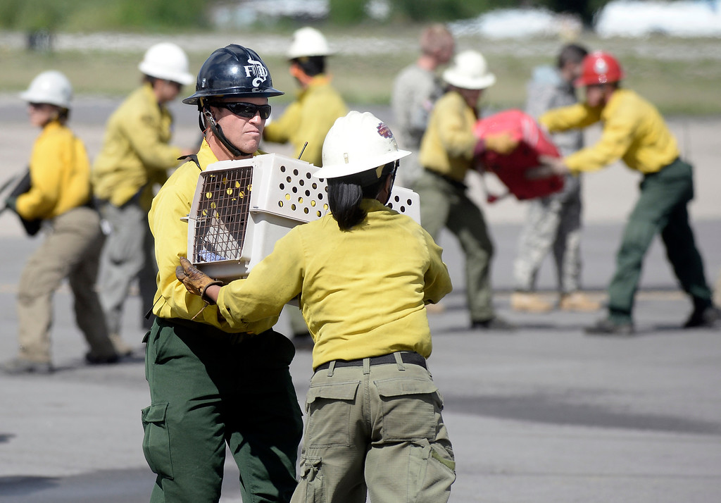 . Rescue workers carry animals and belongings from a helicopter after a rescue mission on Monday, Sept. 16, at the Boulder Municipal Airport in Boulder. For more photos and video of the flood rescue go to www.dailycamera.com Jeremy Papasso/ Camera