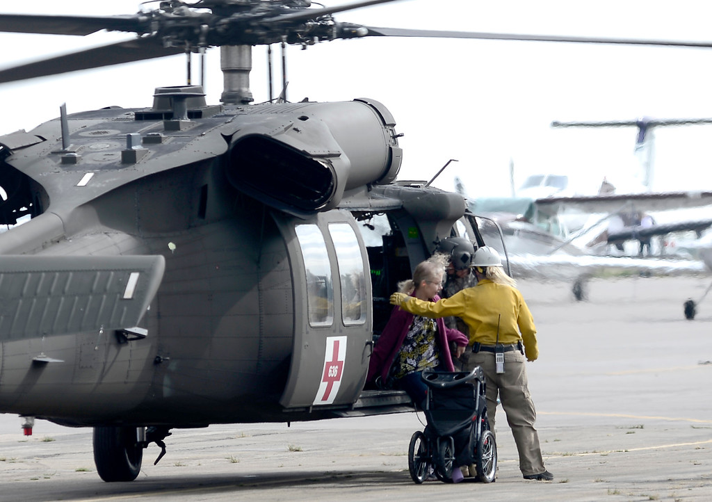 . Ground crew members assist a woman rescued from one the mountain towns from a National Guard helicopter at Boulder Municipal Airport  in Boulder, Colorado September 14, 2013. Many small mountain towns are cut off from road access and people can only be brought out by air.  BOULDER DAILY CAMERA/ Mark Leffingwell