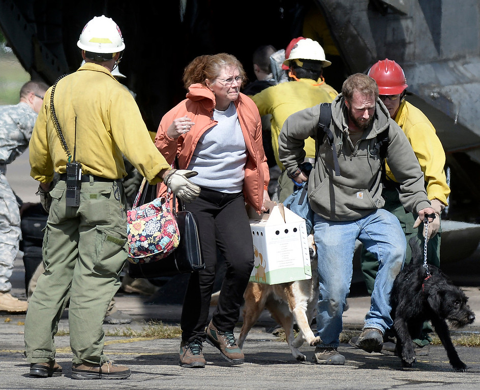 . Evacuees hurry across the tarmac after being rescued by helicopter from the Pinewood Springs area on Monday, Sept. 16, at the Boulder Municipal Airport in Boulder. For more photos and video of the flood rescue go to www.dailycamera.com Jeremy Papasso/ Camera
