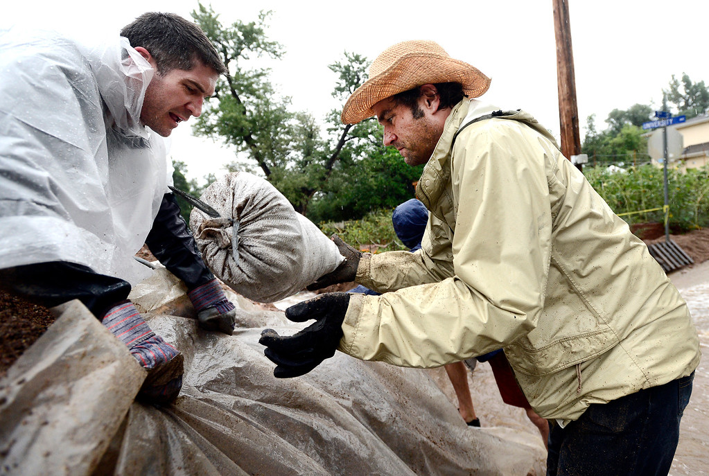 . Tim Eggert, right, carries a sand bag as Ed von Bleishert, left, holds plastic tarp on a berm as residents reinforce the dam on 7th Street on University Hill in Boulder, Colorado on Sunday September 15, 2013.  Rain fell heavily again today increasing fears of more flooding in the community. Photo by Paul Aiken / The Daily Camera / Saturday September 15, 2013