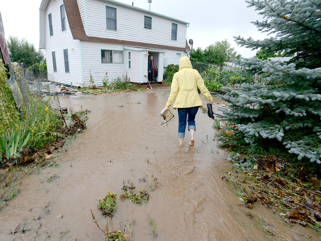 . Chaah Hinseth walks through ankle deep water to get to her home to see how much water damage there is after heavy rains caused severe flooding in Boulder, Colorado September 12, 2013. BOULDER DAILY CAMERA/ Mark Leffingwell