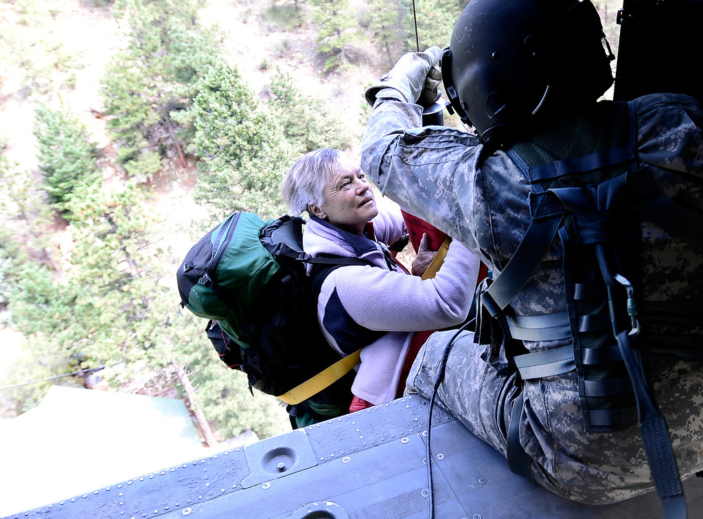 . SFC Keith Bart helps a woman who was winched up to a helicopter flown by members of 2-4 GSAB 4th Infantry Division based in Ft. Carson in near Jamestown, Colorado September 17, 2013. BOULDER DAILY CAMERA/ Mark Leffingwell
