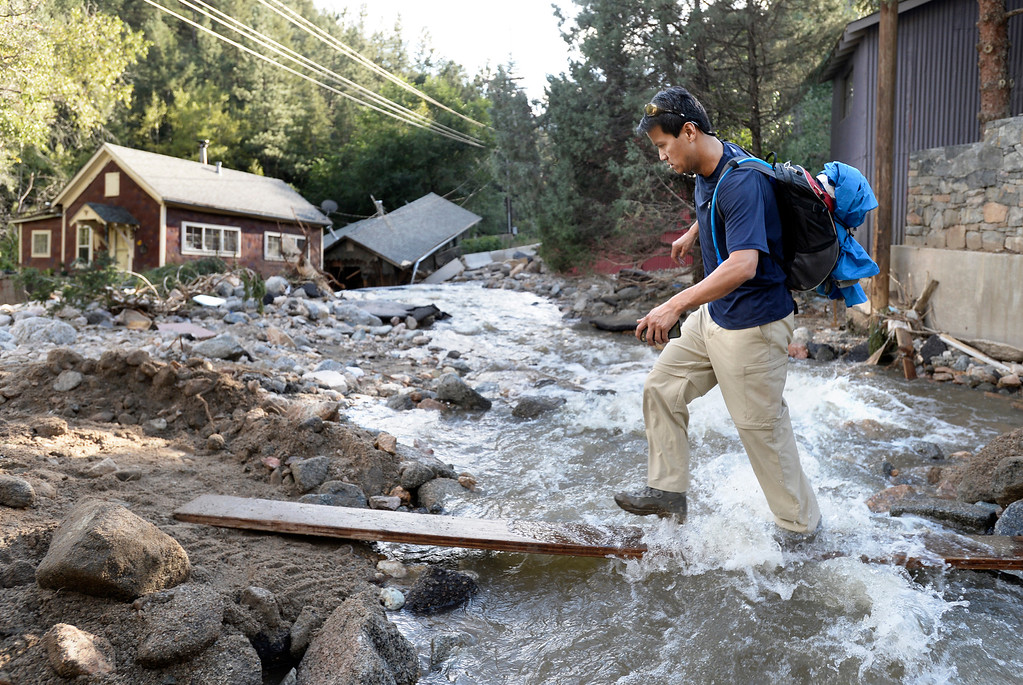 . Keenan Gates walks across a makeshift bridge in Salina after assessing the damage to his mothers home on Tuesday, Sept. 17, at the Salina Junction in the Fourmile Canyon area of Boulder County. For more photos and video of the flood rescue go to www.dailycamera.com Jeremy Papasso/ Camera