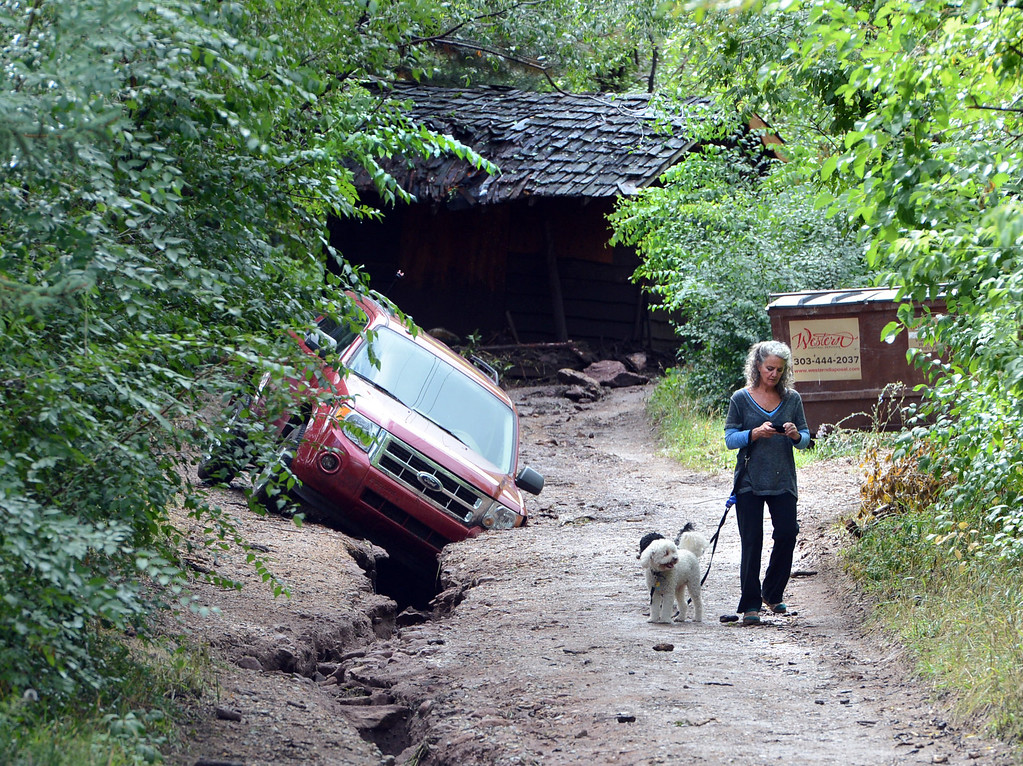 . A woman walks her dogs past a car that  is stuck in a wash out in front of an old wooden shack that washed down a road behind this scene near 3rd and Arapahoe Rd in Boulder. For more flooding videos and photos, www.dailycamera.com. Cliff Grassmick  / September 13, 2013