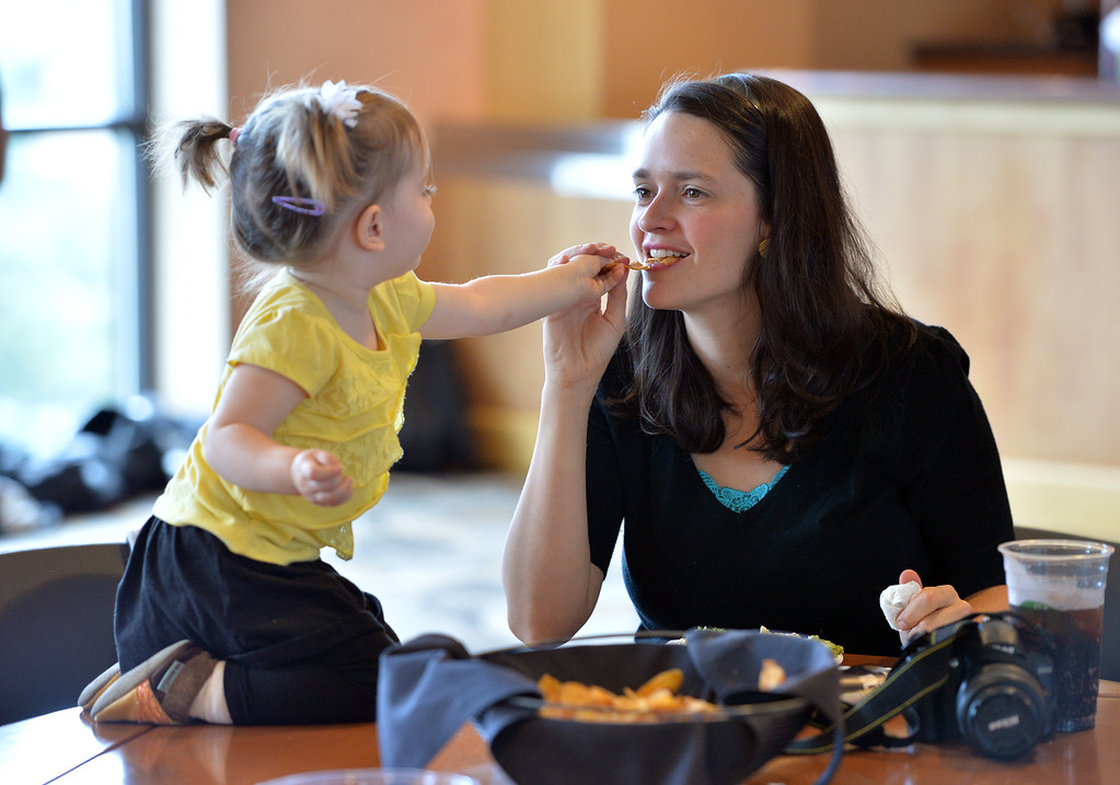 . Amia Hensberry, 21 months old, gives her mother, Karina, a potato chip from her meal served by CU Athletes to the residents of CU�s Family Housing in the Club Room at Folsom Stadium on Saturday. There was extra food  due to the postponement of the football game.  September 14, 2013 staff photo/ David R. Jennings