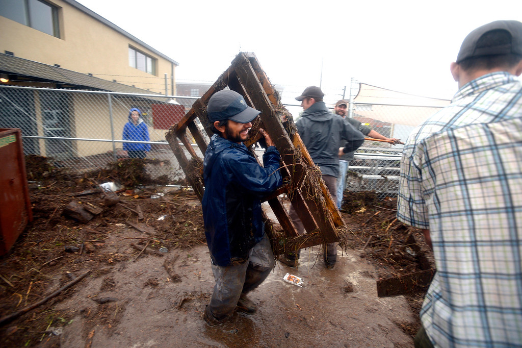 . Jason Ortiz with Namaste Solar carriers debris from behind the business as his coworkers clean up after the flood in north Boulder Thursday morning.  Photo by Paul Aiken / www.dailycamera.com
