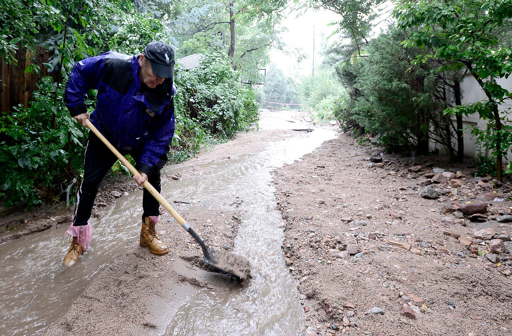 . John McElveen shovels silt and debris out of the path of the rising water as rains pick up in Boulder, Colorado September 15, 2013.  REUTERS/Mark Leffingwell  (UNITED STATES)