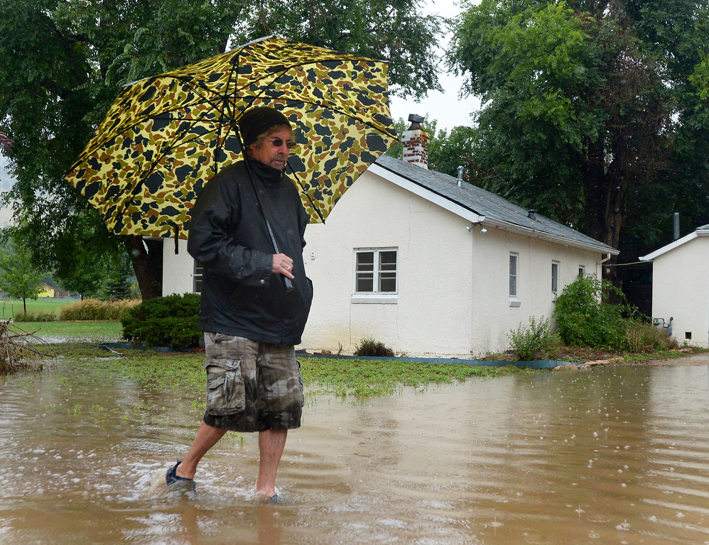 . James Coon, of Boulder, walks in front of a flooded house near the North Boulder Park during the heavy flooding on Thursday in Boulder. For a video of the flooding go to www.dailycamera.com  Jeremy Papasso/ Camera