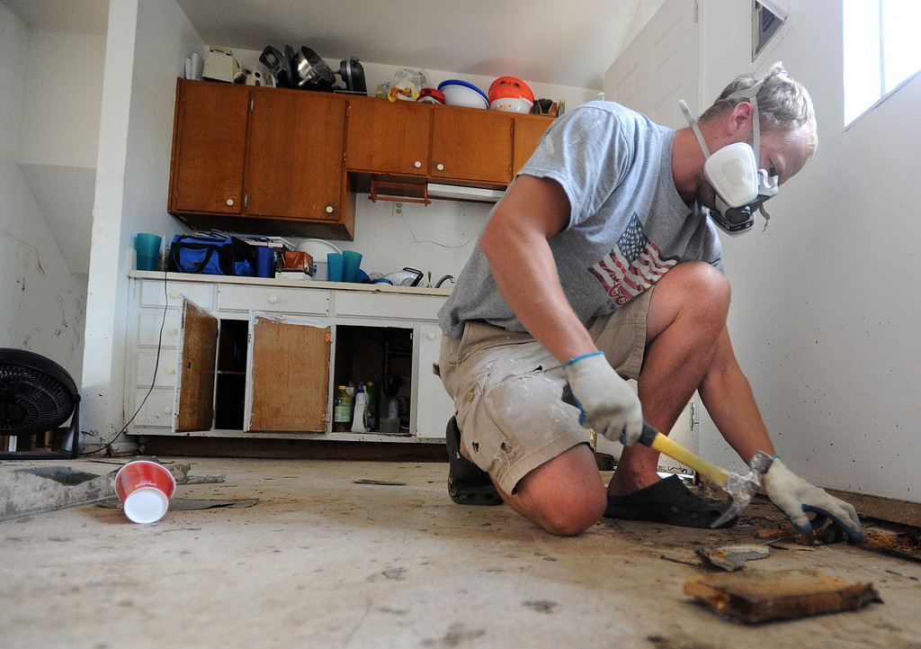 . Property Manager, Jamie McMaster, removes a damaged kitchen floor at a home on Moorhead Ave in Boulder. For more flooding videos and photos, www.dailycamera.com. Cliff Grassmick  / September 19, 2013