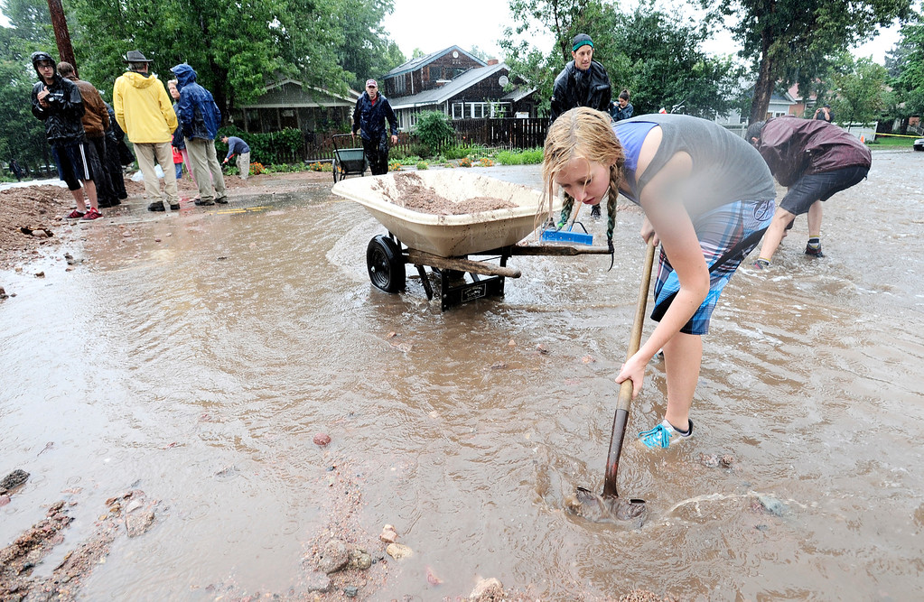 . Malia Clearwater joins her neighbors shoveling wash out debris into a dyke to funnel water down 7th Street at University as heavy rains cause severe flooding in Boulder, Colorado September 12, 2013. BOULDER DAILY CAMERA/ Mark Leffingwell