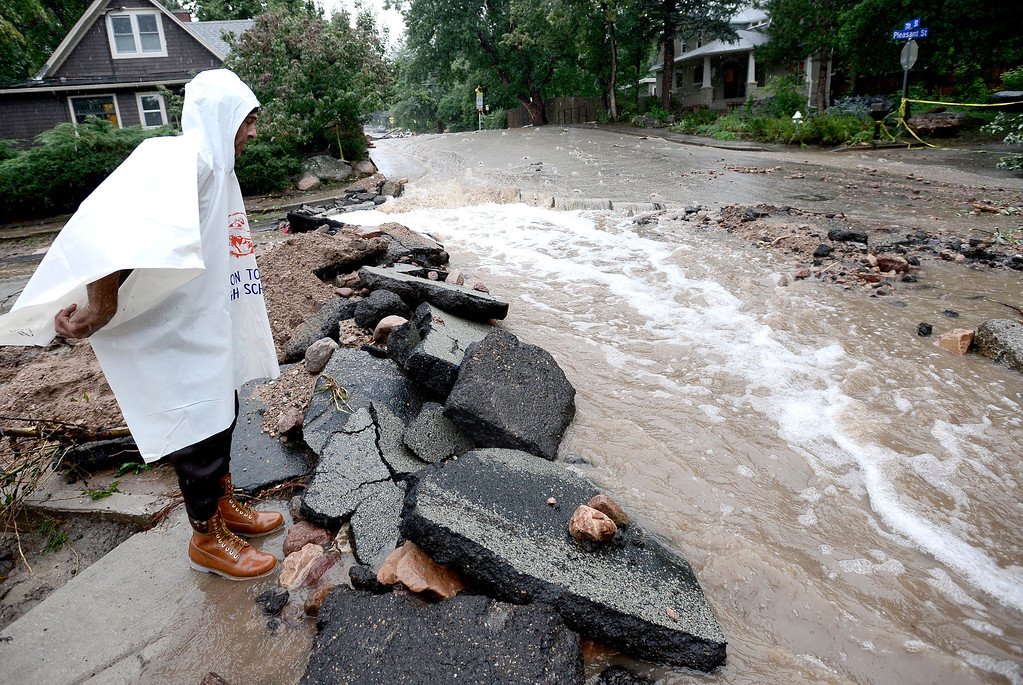 . John Hoffenberg watches the flow of water increase at 7th and Pleasant as rains get heavier in Boulder, Colorado September 15, 2013.  REUTERS/Mark Leffingwell  (UNITED STATES)