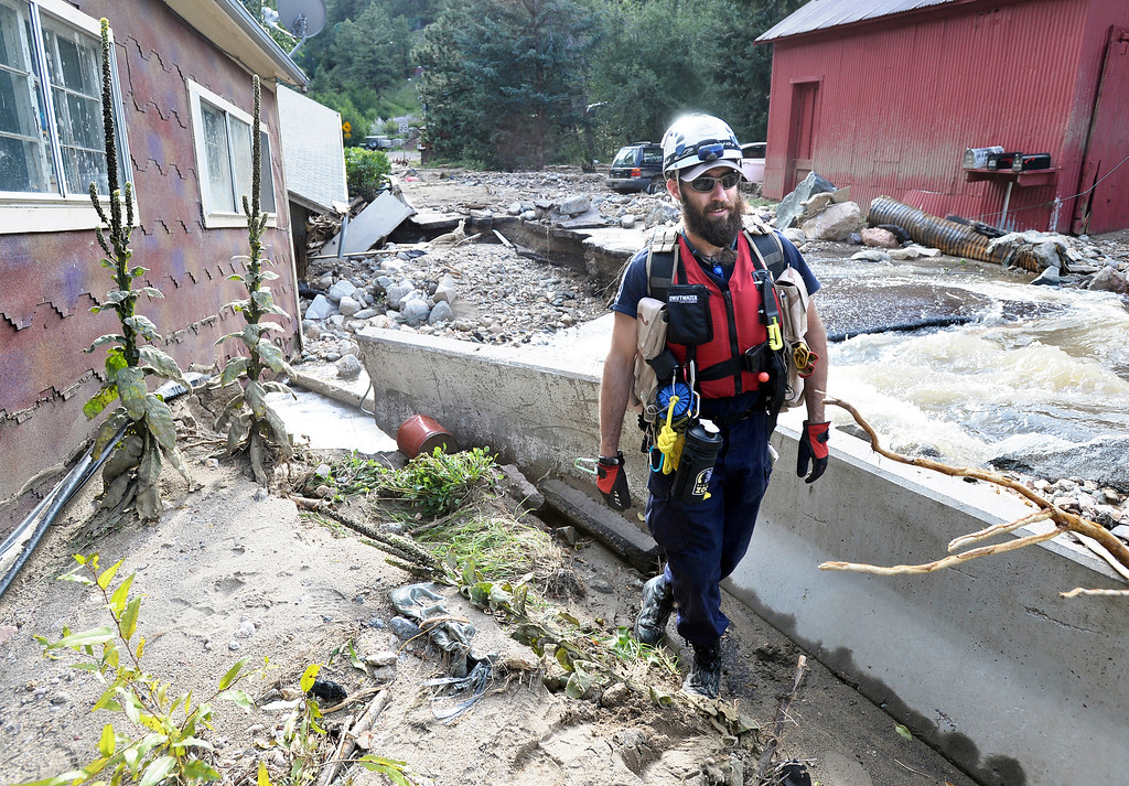 . American Humane Association worker Josh Daniels searches for a missing cat at a home destroyed by the flood in Salina on Tuesday, Sept. 17, on Fourmile Canyon Drive in Boulder County. For more photos and video of the flood rescue go to www.dailycamera.com Jeremy Papasso/ Camera