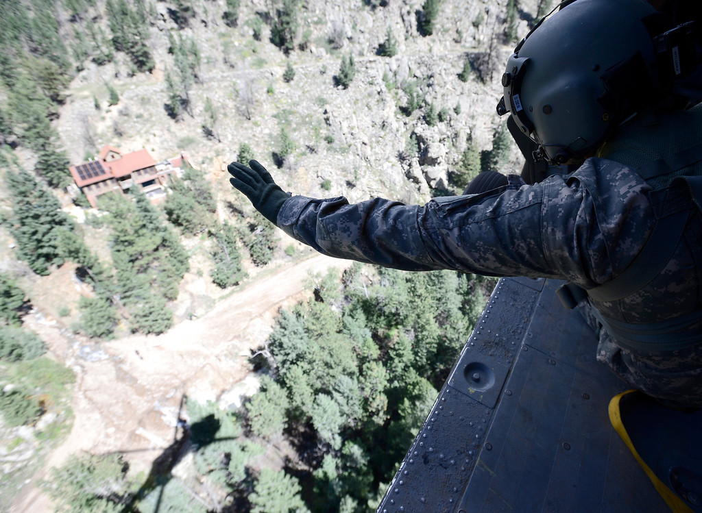 . Staff Sergeant Jose Pantoja, with the 2-4 GSAB 4th Infantry Division based in Ft. Carson, waves to people in Left Hand Canyon after they indicated they were OK and didn\'t need help from a Blackhawk helicopter near Jamestown, Colorado September 17, 2013. BOULDER DAILY CAMERA/ Mark Leffingwell