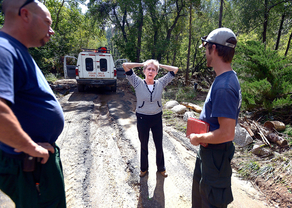 . Local resident Eileen Sharbonda, at center, talks with Four Mile Fire Department\'s Bill Kerwin, left, and Shanti Leasure after being allowed back to her home on Tuesday, Sept. 17, in the Fourmile Canyon area of Boulder County.  Jeremy Papasso/ Camera