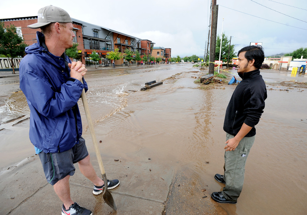 . Josh Ford, left, and Surendra Thapa, both of Namaste Solar in north Boulder, look over the flood waters on Friday. For more flooding videos and photos, www.dailycamera.com. Cliff Grassmick  / September 13, 2013