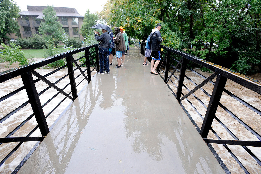 . People watch the flooded Boulder Creek from a bridge near Broadway in Boulder. For more flooding videos and photos, www.dailycamera.com. Cliff Grassmick  / September 12, 2013