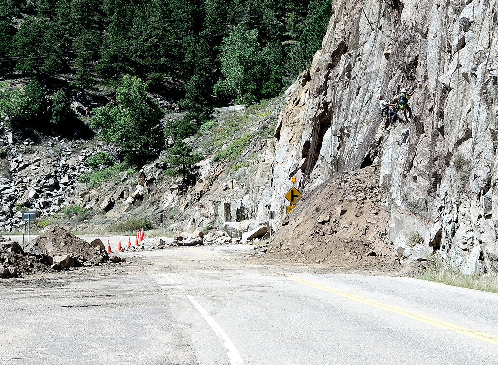. Workers check the rock face where dirt and debris had washed across Boulder Canyon Drive near Magnolia Boulder, Colorado September 18, 2013.  DAILY CAMERA/ MARK LEFFINGWELL