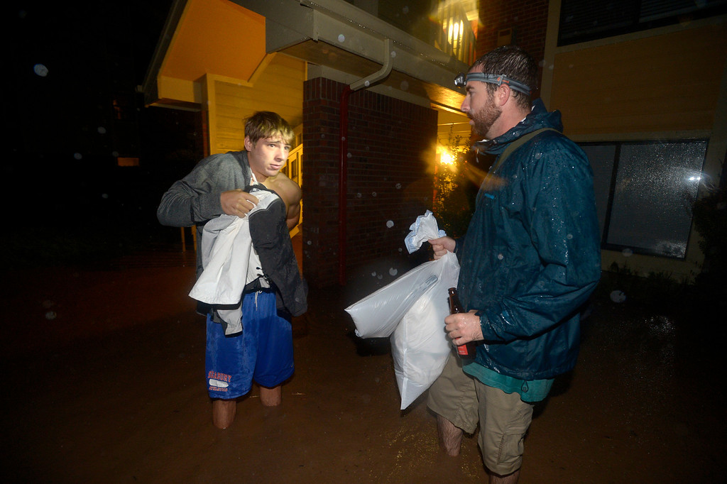 . Dag Larson, right, helps Alek Stefanov gather his belonging from his flooded apartment in the Aspen Grove Apartments off Kalmia Ave in north Boulder Thursday morning. Larson and a friend woke Stefanov from a sound sleep as water poured into his apartment.  Photo by Paul Aiken / www.dailycamera.com