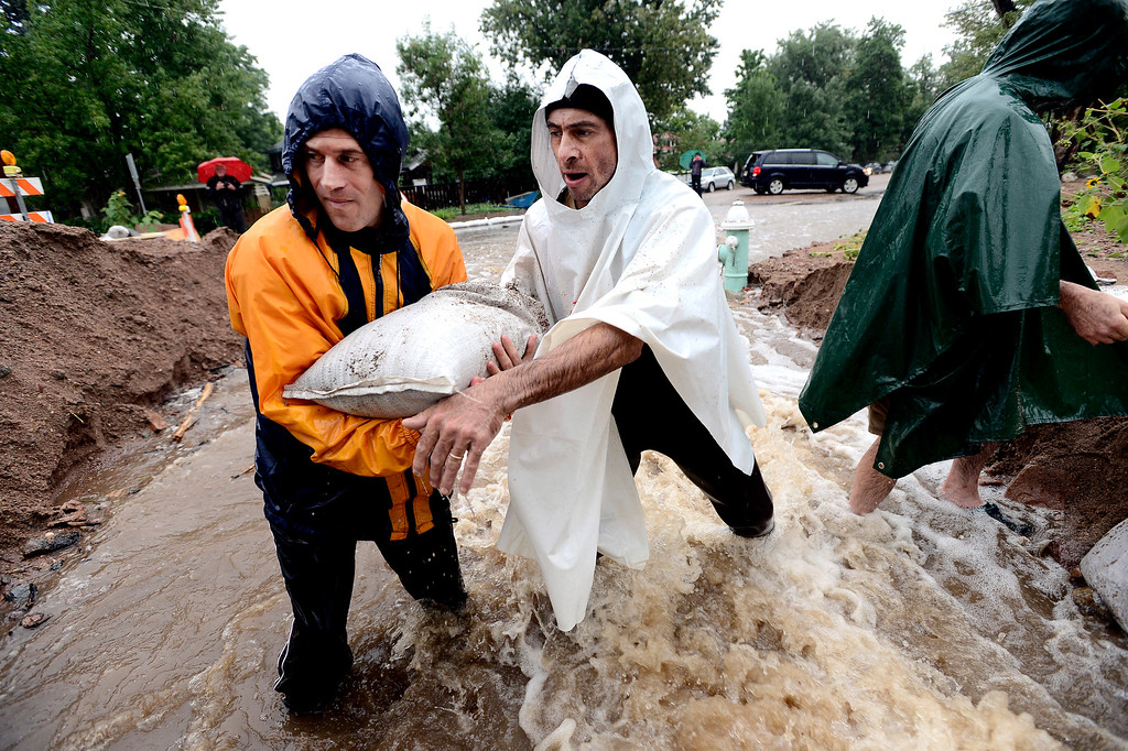 . From left to right Dan Feldheim, Scott Hoffenberg and John Smart pass sandbags as residents reinforce the dam on 7th Street on University Hill in Boulder, Colorado on Sunday September 15, 2013.  Rain fell heavily again today increasing fears of more flooding in the community. Photo by Paul Aiken / The Daily Camera / Saturday September 15, 2013