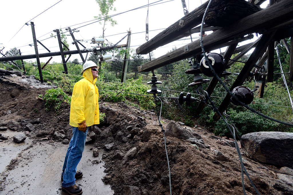 . Justin Slyter with Par Electrical Contractors looks over fallen power poles in a office complex on Arapahoe Avenue next to Eben G Fine Park in Boulder on Saturday.  Photo by Paul Aiken / The Daily Camera / Saturday September 14, 2013