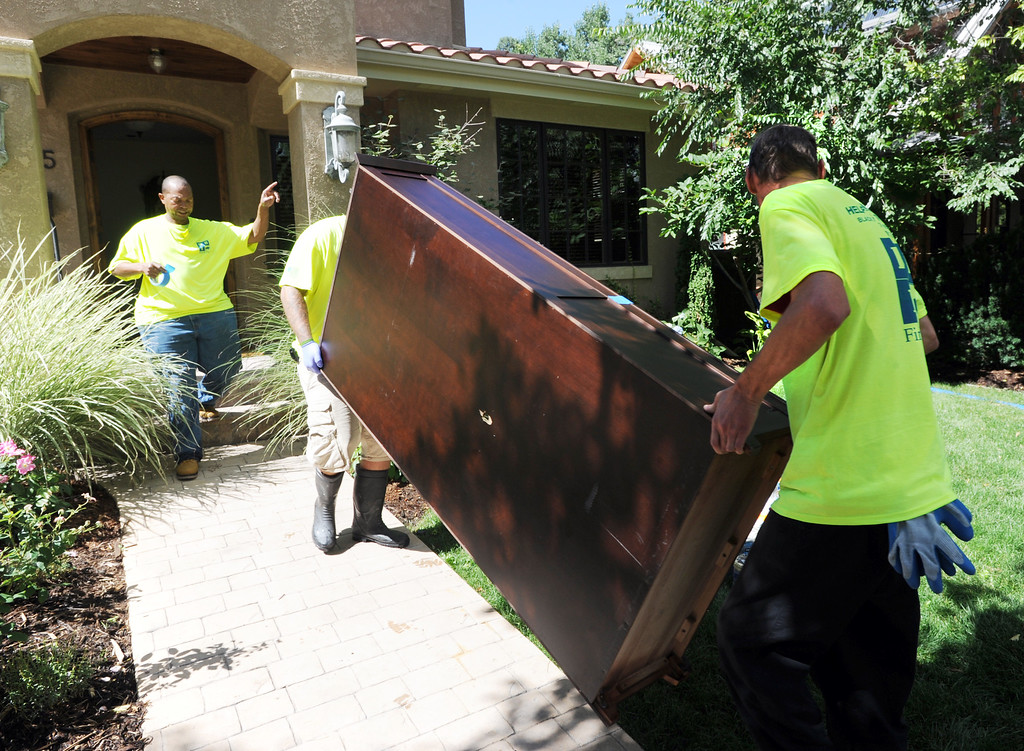 . Ken Daugherty, of Buffalo Builders Inc, flood and fire catastrophe team, directs Juston Travis and James Van Engen, where to  move out damaged furniture at a Boulder home near North Boulder Park.  For more flooding videos and photos, www.dailycamera.com. Cliff Grassmick  / September 18, 2013
