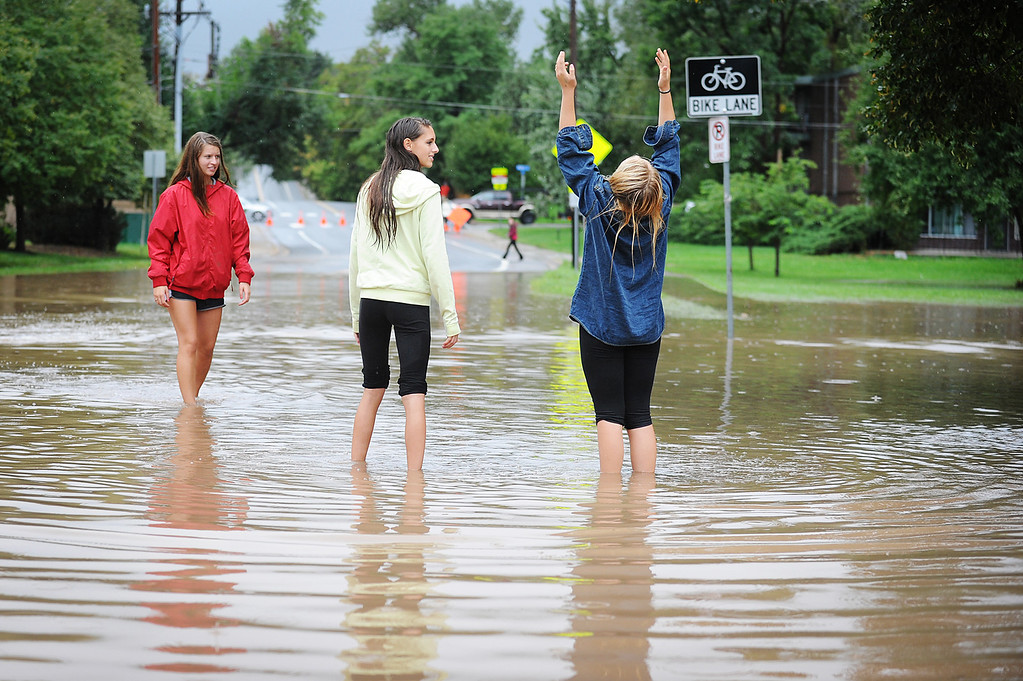 . From left, 15-year-olds Rosey Mills, Valentine Lambert and Jade Hunter play in the flood waters at the corner of Balsam and 9th Street in Boulder on Thursday, September 12, 2013. (Kira Horvath/ Daily Camera)