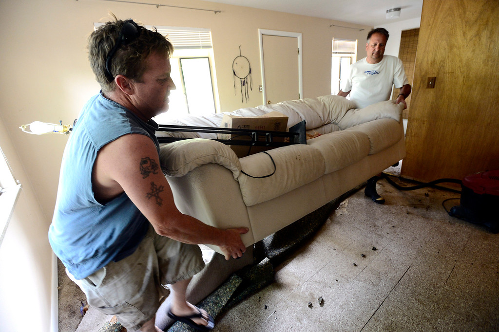 . From left to right Patrick Muir and Steve Gabel move a soaked couch out from Muir\'s apartment on 7th Street on University Hill in Boulder on Saturday. Gabel a neighbor came in to lend a hand.  Photo by Paul Aiken / The Daily Camera / Saturday September 14, 2013