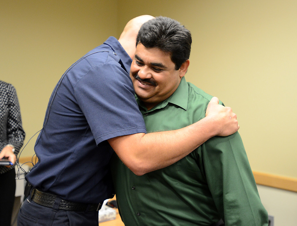 . North Metro Fire Rescue engineer John Cook, left, gives Roy Ortiz a hug after a news conference at Good Samaritan Hospital on Friday. Ortiz was rescued by Cook after being trapped in the water of Rock Creek at Dillon Road on Thursday. September 13, 2013 staff photo/ David R. Jennings
