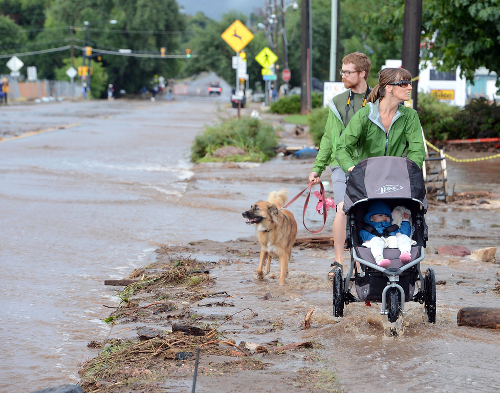 . Kimberly Meyers, her husband, Traeger, and baby Harper, walk along North Broadway to survey the flood damage on Friday morning. For more flooding videos and photos, www.dailycamera.com. Cliff Grassmick  / September 13, 2013