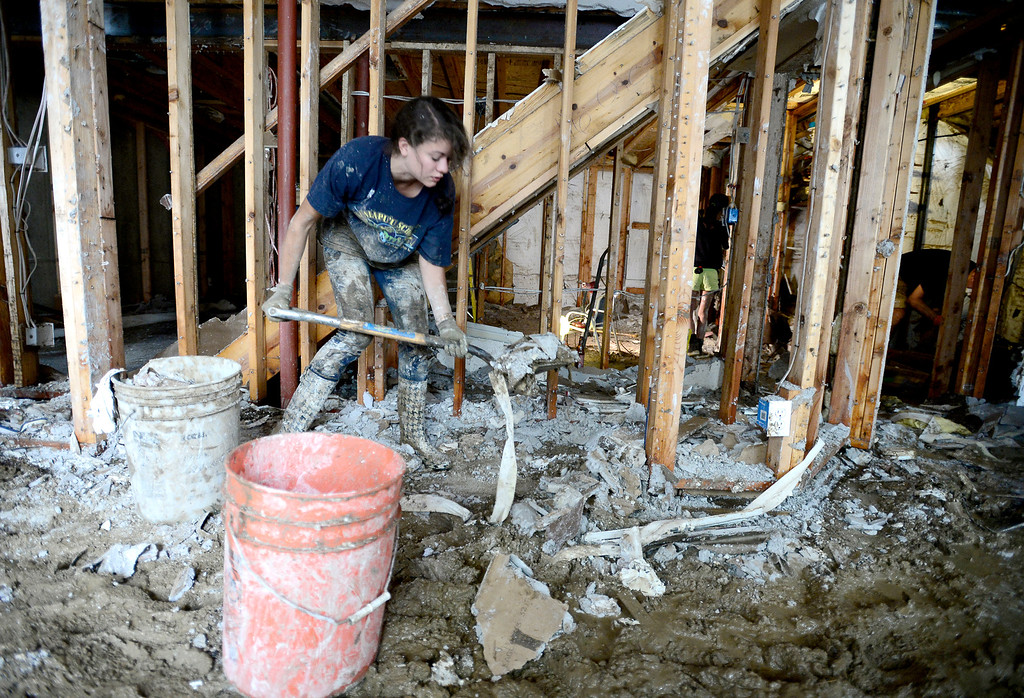. Dakota Walters shovels mud and debris into 5-gallon bucks at her Aunt and Uncle\'s home after their basement was flooded with 8-feet of water on Qualla Drive in Boulder, Colorado September 14, 2013. BOULDER DAILY CAMERA/ Mark Leffingwell
