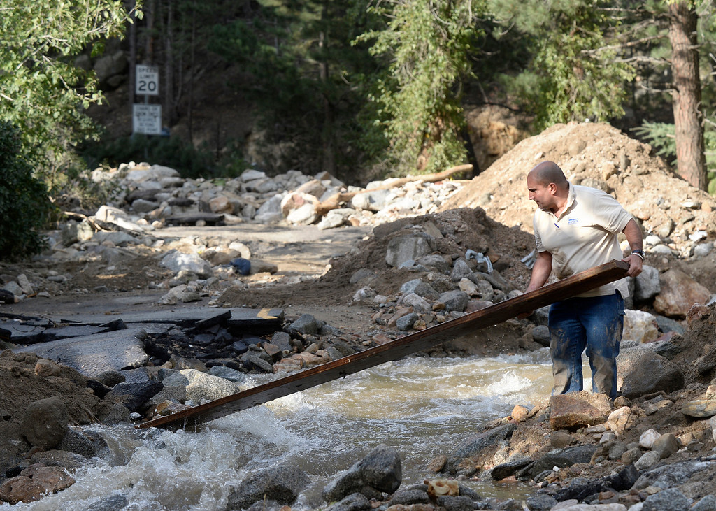 . James DiBella, with the National Flood Insurance Program, works to place a makeshift bridge back in its place on Tuesday, Sept. 17, in the town of Salina. For more photos and video of the flood rescue go to www.dailycamera.com Jeremy Papasso/ Camera