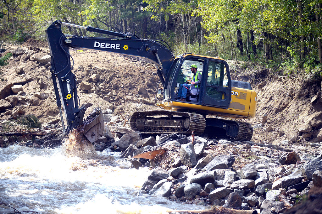 . Boulder County worker Matt Linton works to repair a road destroyed by the flood in Salina on Tuesday, Sept. 17, in the Fourmile Canyon area of Boulder County.  Jeremy Papasso/ Camera
