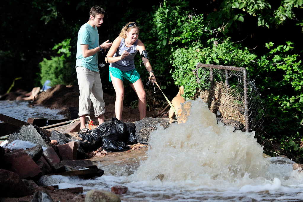. Marina Leigh keeps her dog Juno out of the rushing water in a homemade dam on 7th Street as Nick Minton looks on on University Hill in Boulder on Saturday.  Photo by Paul Aiken / The Daily Camera / Saturday September 14, 2013