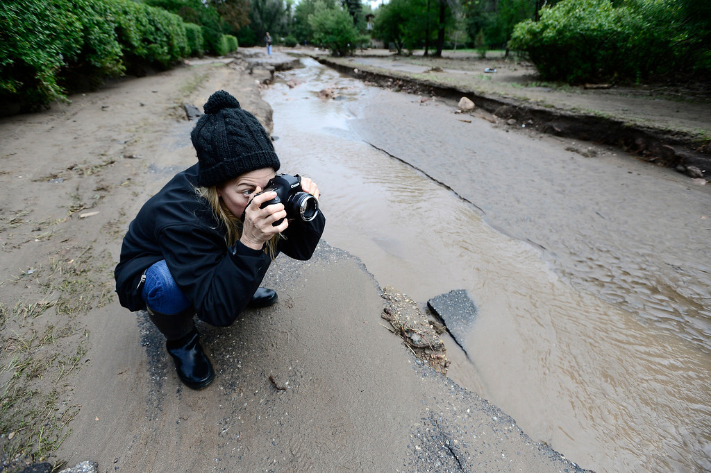 . Jessica Young takes photos of what is left of Topaz drive in Boulder, Colorado on Sunday September 15, 2013.  Rain fell heavily again today increasing fears of more flooding in the community.  Photo by Paul Aiken / The Daily Camera / Saturday September 15, 2013