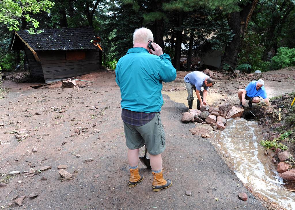 . Residents in the west Arapahoe neighborhood try to redirect the run off. The shack on the left was washed down about 100-yards from its original location. For more flooding videos and photos, www.dailycamera.com. Cliff Grassmick  / September 13, 2013