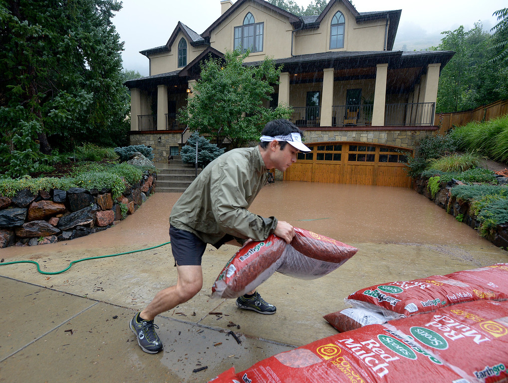 . Dan Fox, of Boulder, places bags of mulch in his neighbors driveway to prevent more flooding during the heavy flooding on Thursday in Boulder. For a video of the flooding go to www.dailycamera.com  Jeremy Papasso/ Camera