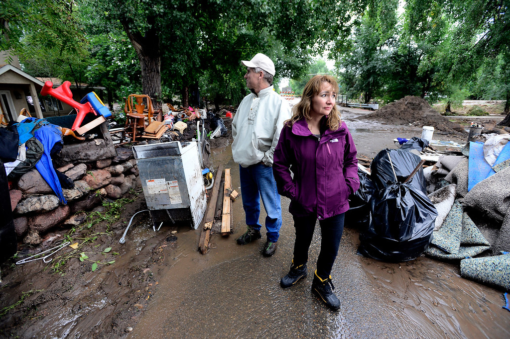 . Granger and Suzie Banks walk between discarded and drying household items from a damaged house on Upland Ave in Boulder, Colorado on Sunday September 15, 2013.  Rain fell heavily again today increasing fears of more flooding in the community. Photo by Paul Aiken / The Daily Camera / Saturday September 15, 2013