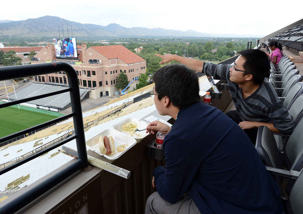 . Jie Lu ,left, and Kangqian Wu watch a football game broadcast on to screens at Folsom Stadium as well as National Guard helicopters flying rescue missions over the mountains. Residents of CU�s Family Housing were served  meals by CU athletes in the Club Room at Folsom Stadium on Saturday due to the postponement of the football game.  September 14, 2013 staff photo/ David R. Jennings