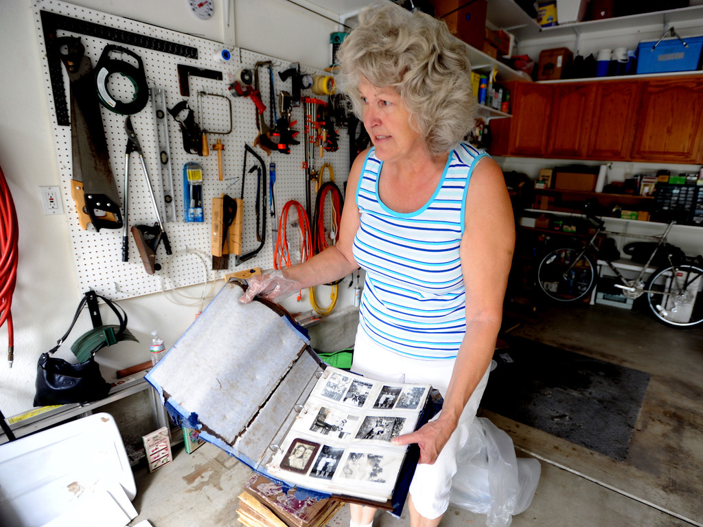 . Rose Marie Rempel holds an old photo album that has water damage from the flooding on September 14, 2013. She lives in the Champion neighborhood in Longmont, Colorado. Cliff Grassmick / September 14, 2013