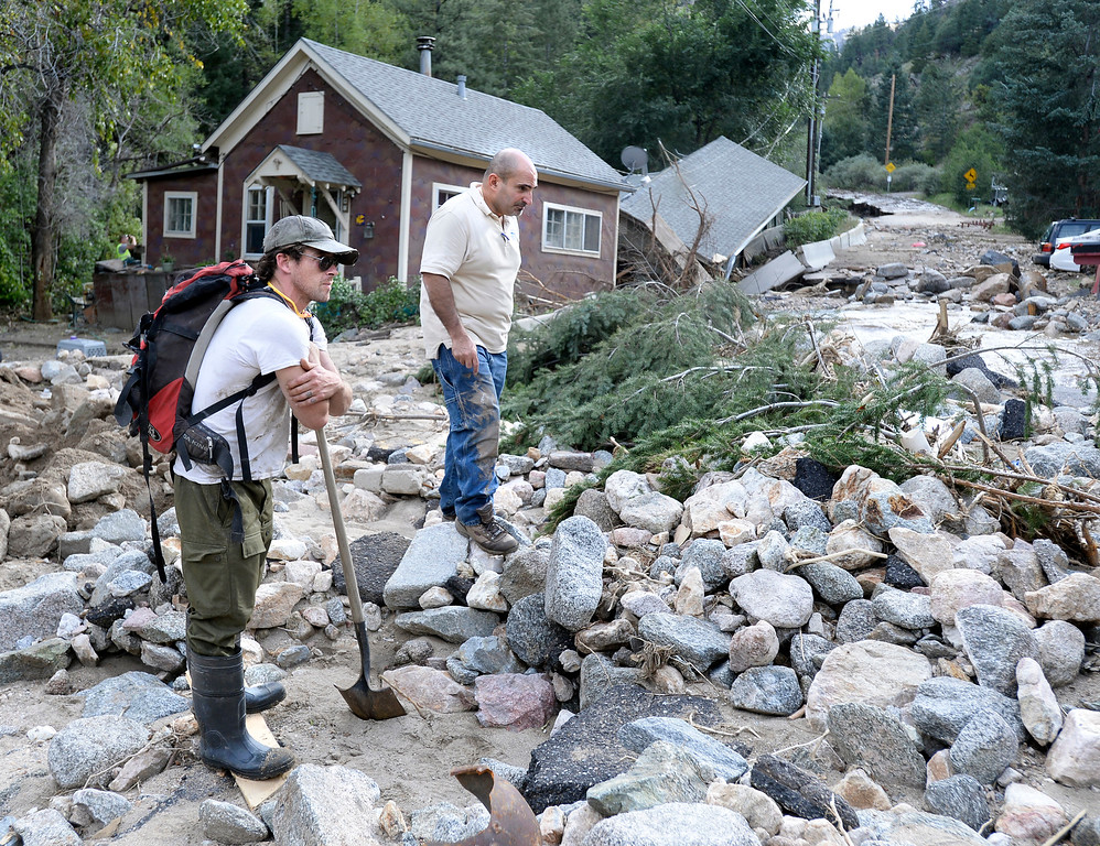 . Local resident, name not given, at left, and insurance adjuster James DiBella look at the destroyed road in Salina on Tuesday, Sept. 17, on Fourmile Canyon Drive in Boulder County. For more photos and video of the flood rescue go to www.dailycamera.com Jeremy Papasso/ Camera