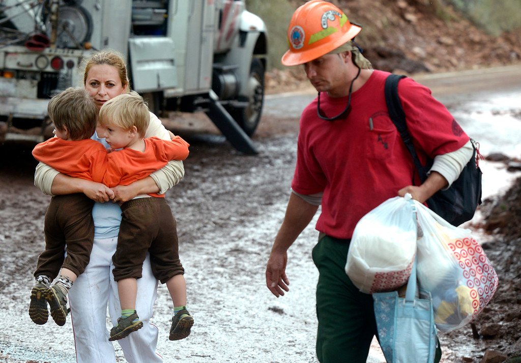. A woman, who asked not to be identified, carries two children while being evacuated by the Juniper Valley Fire Crew on Saturday, Sept. 14, on Olde Stage Road in Boulder. For more photos and video of the flood rescue go to www.dailycamera.com Jeremy Papasso/ Camera